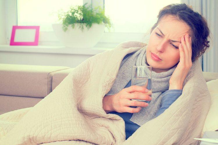 Frau liegt auf Couch mit Glas Wasser in der Hand und ist krank wegen Biowetter